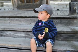 Van Sporting His Junior Ranger Badge on the Steps of a Cabin at the Museum of the Rockies in Bozeman, Montana
